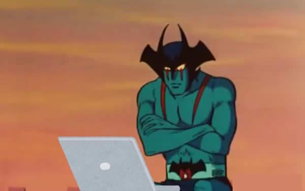 腕組みをしながらノートパソコンを見るデビルマン